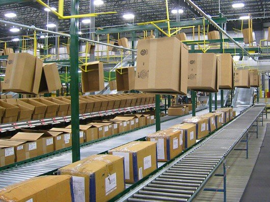 Overhead conveyors deliver empty cartons to order pickers in distribution centers