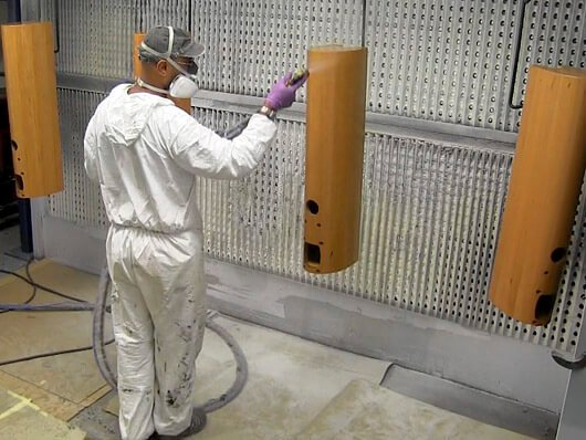 Overhead conveyors handle wood furniture items through paint finishing processes