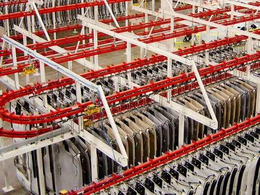 Overhead conveyor provides live storage and parts buffering between manufacturing operations.