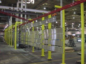 Power and free overhead conveyor carrying long parts through washer system