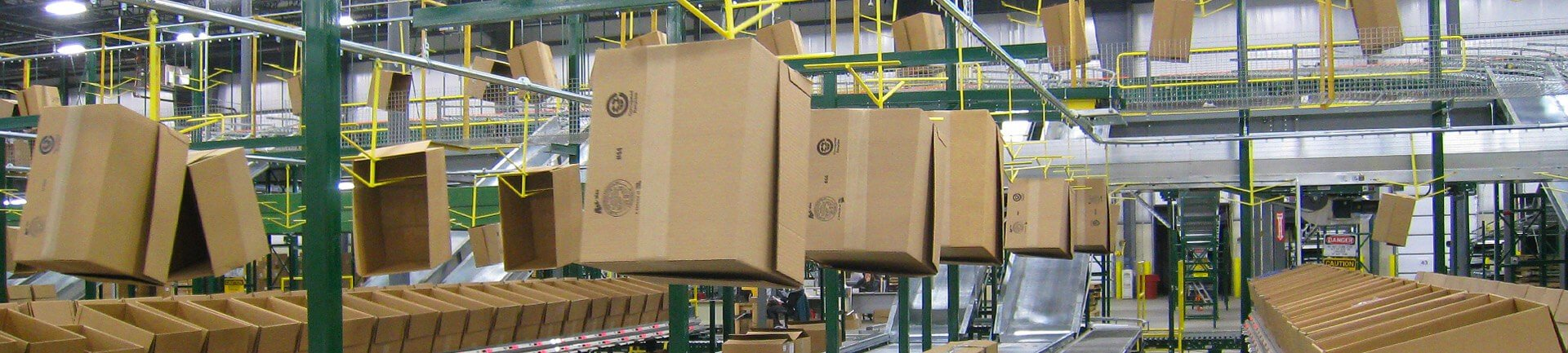 Overhead conveyor for empty carton delivery in split case picking operations.