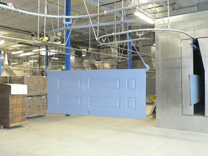 Enclosed track overhead conveyor for wet spray painting line.