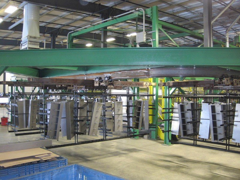 I-beam conveyor transports heavy racks through a cleaning process.