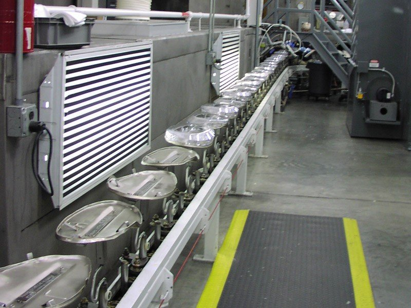 Heavy duty inverted conveyor carrying metal parts through a chemical wash.