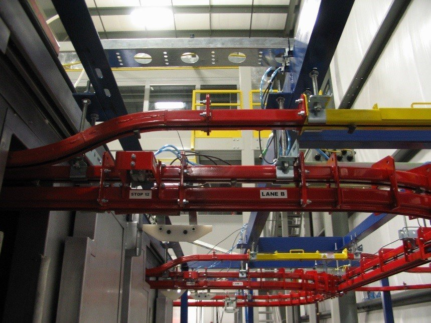 Power and free overhead conveyor for wet spray application.
