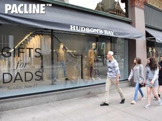 Pedestrians view The Hudson's Bay creative window display created using a PAC-LINE™ overhead conveyor.