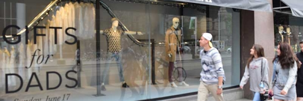 Pedestrians view The Hudson's Bay creative window display created using a PAC-LINE™ overhead conveyor.
