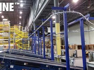 Empty box overhead conveyor integrated with equipment.