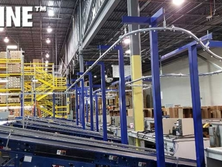 Empty box enclosed track overhead conveyor integrated with equipment.
