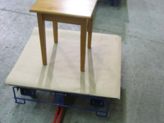 Towline system with rotating carts used to convey these awkward shaped furniture pieces through assembly and finishing.