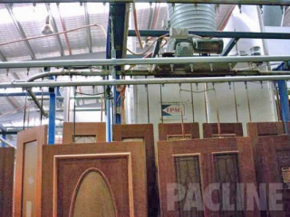Large wooden doors hang from Pacline enclosed track conveyor to transport from finishing through assembly process