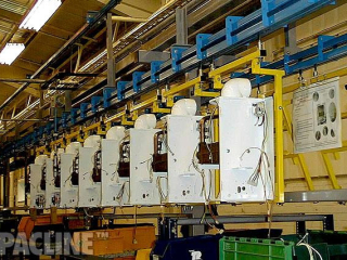 A PACLINE Power and Free conveyor carrying large water heaters through assembly process.