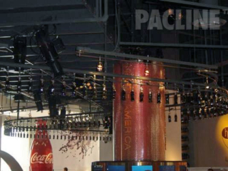 Hundreds of bottles of Coca Cola are carried overhead on a continuously moving PAC-LINE™ overhead conveyor.