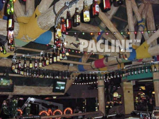 A PAC-LINE™ conveyor keeps beer bottles moving continuously overhead in bar for a creative display.