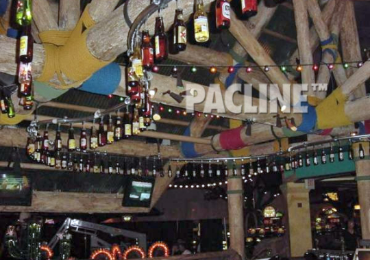 A PAC-LINE™ decorative conveyor keeps beer bottles moving continuously overhead in bar for a creative display.
