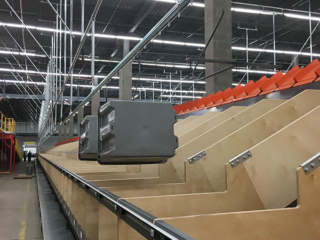 Empty tote conveyor delivering totes to operators at chutes from a tilted tray sorter.