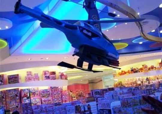 An decorative overhead conveyor carries a Helicopter above store patrons in a Macau toy store.