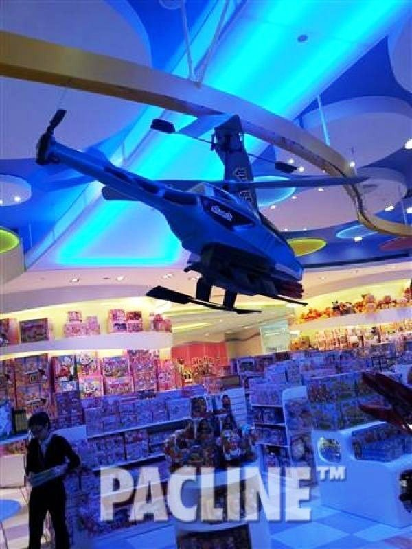 An overhead conveyor carries a Helicopter above store patrons in a Macau toy store.