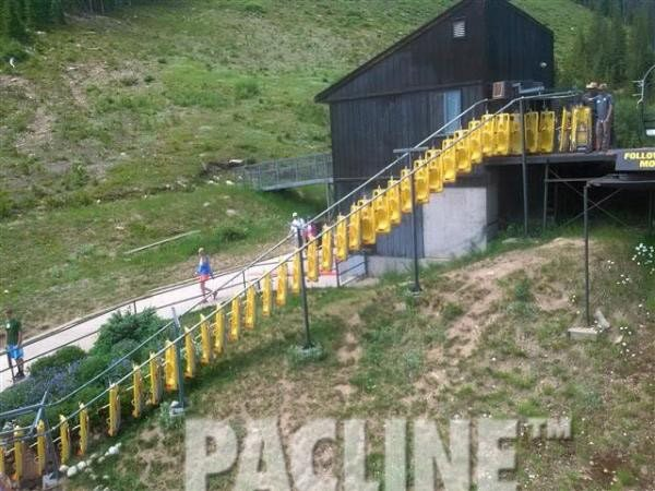 Alpine sleds being conveyed uphill by The PAC-LINE™ enclosed track overhead conveyor to waiting patrons.