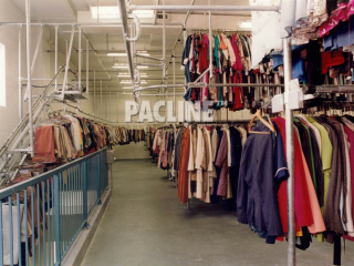 Garment storage and retrieval conveyor takes items up steep incline to second floor warehouse.