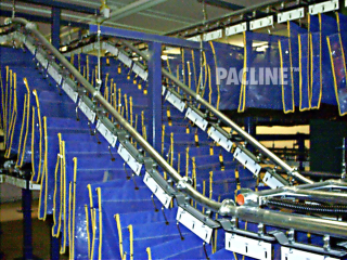 Garment bags are transported from floor level up steep incline for efficient storage in unused ceiling area.