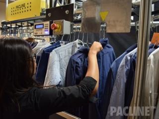 Loading garments on automated uniform distribution conveyor.