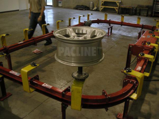 Sideways oriented, enclosed track conveyor for finishing automotive rims on sprocket rotatable spindles.