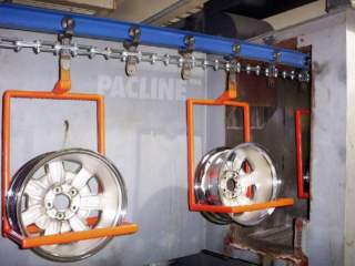 Overhead monorail conveyor carries auto wheel rims through wash system before electroplating process.