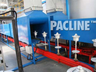 A PAC-MAX conveyor with a slot-side configuration, conveys product through the stages of a powder coating finishing