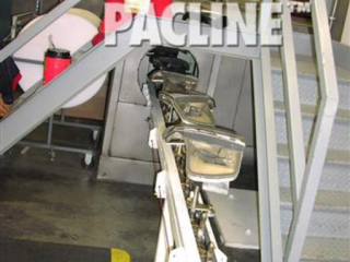 An automotive finishing line uses a PAC-MAX enclosed track conveyor to transport light bezels into a spray booth.