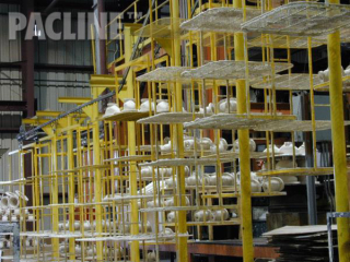 Finishing of pipe fittings on multi-tiered carrier using The PAC-LINE™ enclosed track conveyor.
