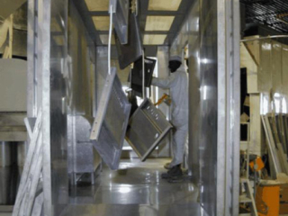 PACLINE's enclosed track overhead conveyor carries storage locker parts through powder coating finishing line.