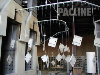 The PACLINE overhead conveyor is perfect for this powder coating application on storage locker components.