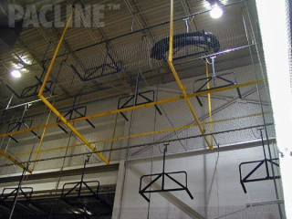 Overhead conveyor system transporting automotive fascia from molding machines to shipping using overhead space.