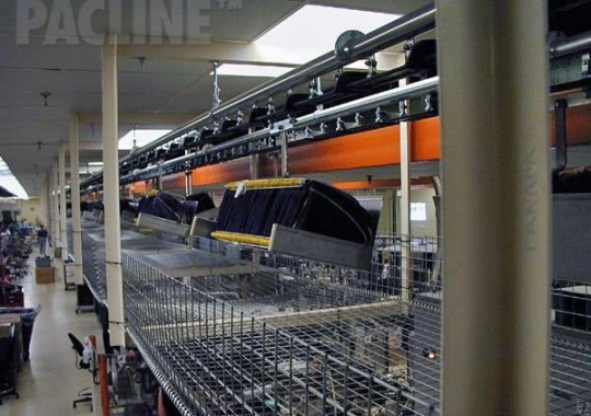 Moving beverage bottle bags from warehouse to assembly onto bottles using enclosed track conveyor system.