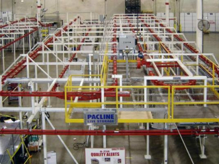 Overhead power and free conveyor system used for live storage of automotive parts.
