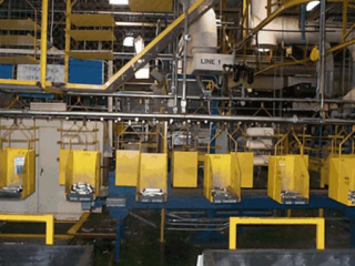 Buffer accumulation and delivery of head rest support rods for automotive seats using overhead conveyor system.
