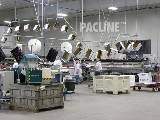 Conveyor moves empty cartons on hooks in apple packing shed.