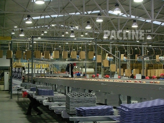 Apple packing house uses conveyor to transport empty cartons.