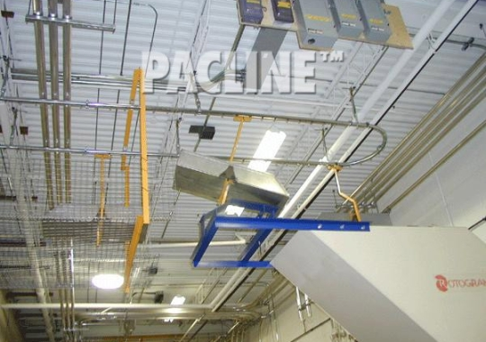 PACLINE's overhead conveyor removes plastic scrap and dumps waste into grinder for recycling.