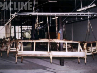 Enclosed track overhead conveyor transfers wooden sofa frames through paint finishing lines.