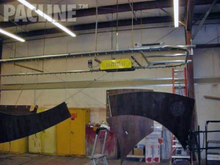 Large custom counter tops are moved through paint line process on Pacline overhead conveyor.