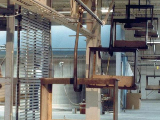 An overhead conveyor can handle steep inclines to move these frames up off the floor between finishing processes.
