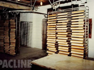The PAC-LINE™ paint line conveyor installed with a rack handling system for handling wood chair seats.
