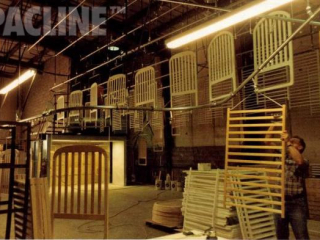 Monorail enclosed track conveyor moves wooden bed frames through sanding and paint finishing.
