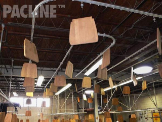 Overhead conveyor system eliminates the need for rack drying on floor. The conveyor also conserves floor space.