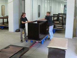 Wooden desks are lightly sanded on towline conveyor system with carts in transit.