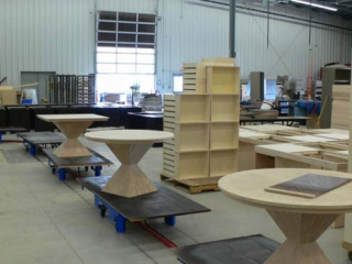 Wood furniture is manually loaded onto slow moving carts on this towline wood finishing conveyor.