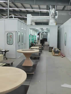 towline conveyor system carrying wooden furniture through painting line