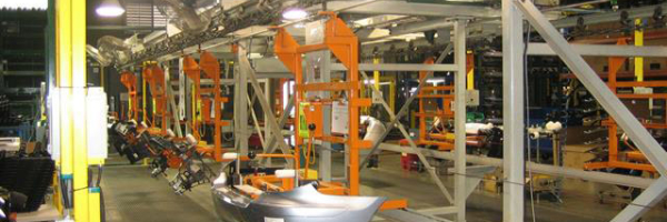 Overhead I Beam trolley conveyor transports large automobile bumpers through assembly process